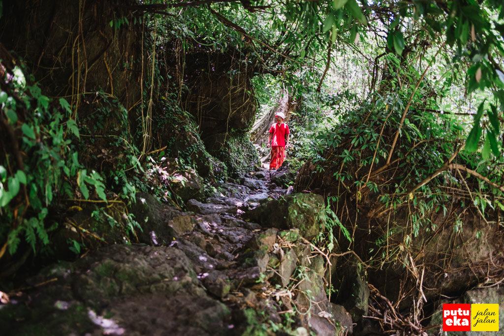 Putu Eka Jalan Jalan sedang berada diantara bebatuan dan juluran akar dari pepohonan
