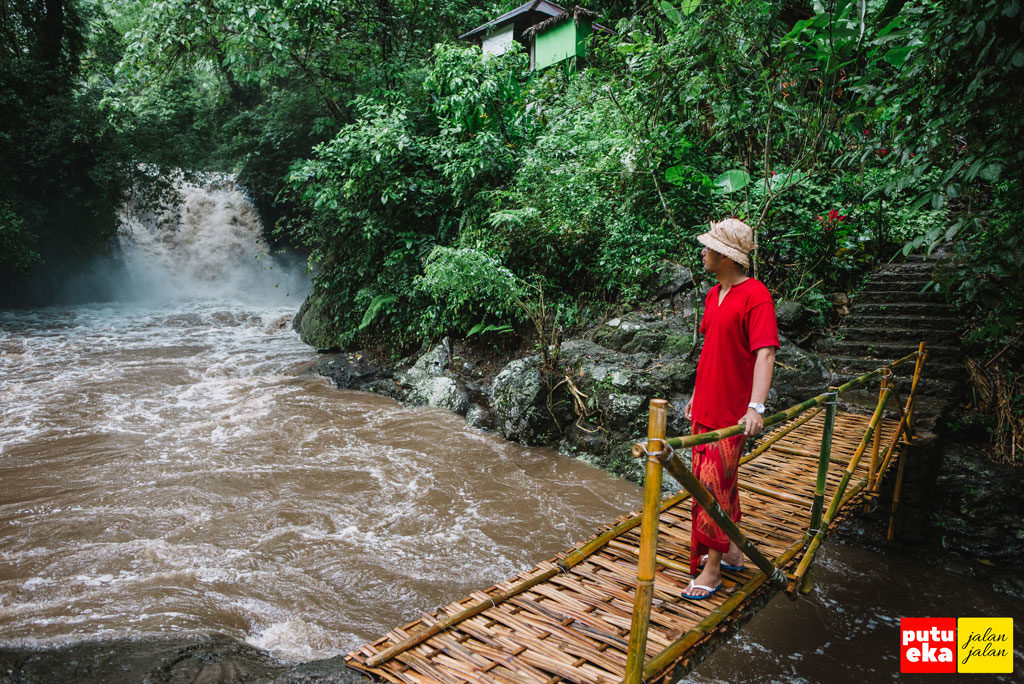 Putu Eka Jalan Jalan sedang berjalan diatas jembatan bambu di bagian hilir air terjun
