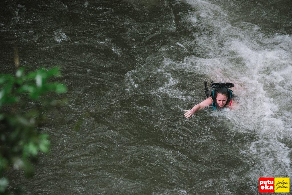 Wisatawan mancanegara sedang berenang ketepian setelah meluncur dari puncak air terjun