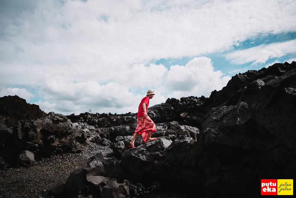 Menaiki bebatuan Taman Lava Hitam dengan hati-hati