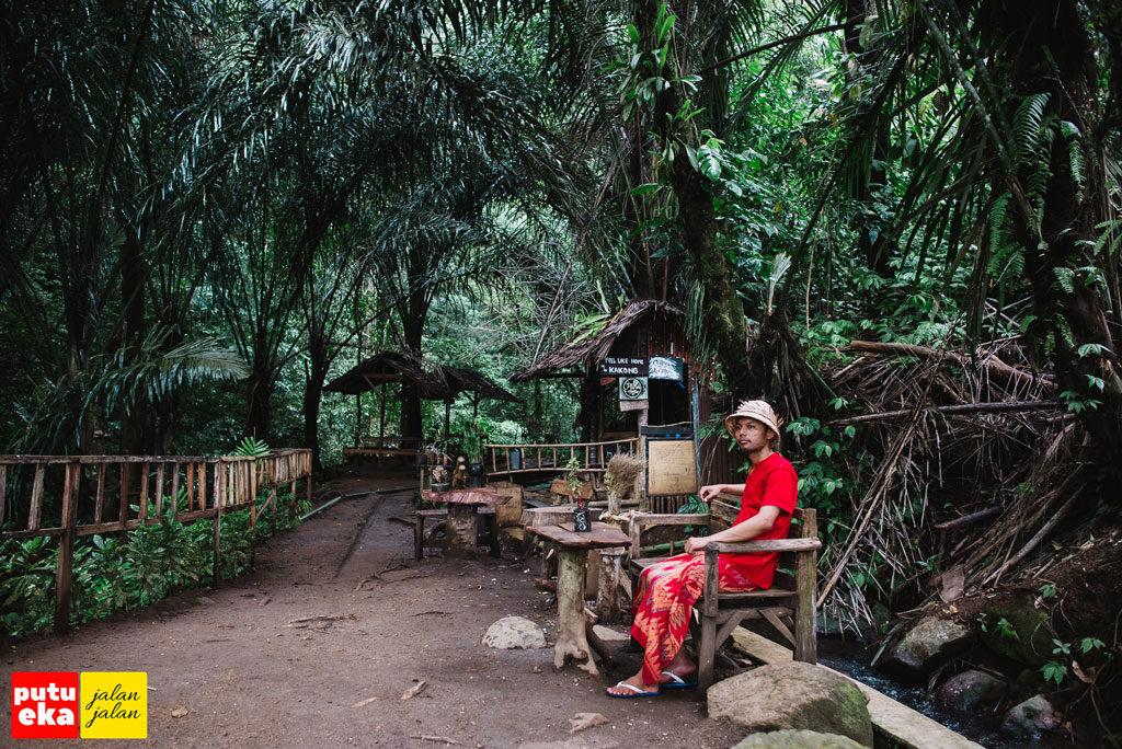 Putu Eka Jalan Jalan dudk di bangku kayu di mata air Medjet Kakong