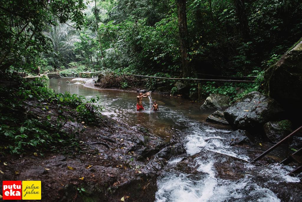 Putu Eka Jalan Jalan sedang bermain air bersama anak kecil warga sekitar