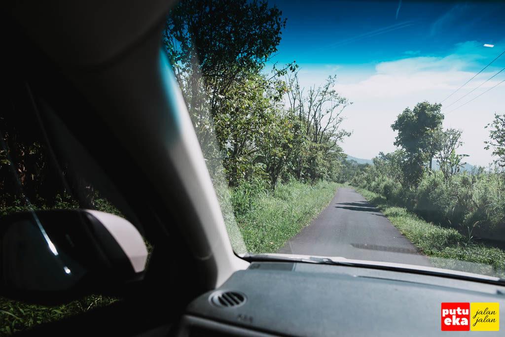 Jalanan beraspal mulus Nampak dari dalam kendaraan