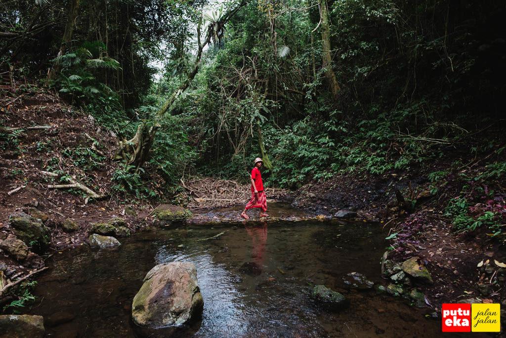 Putu Eka Jalan Jalan menyeberangi batu yang dipakai untuk membendung aliran air