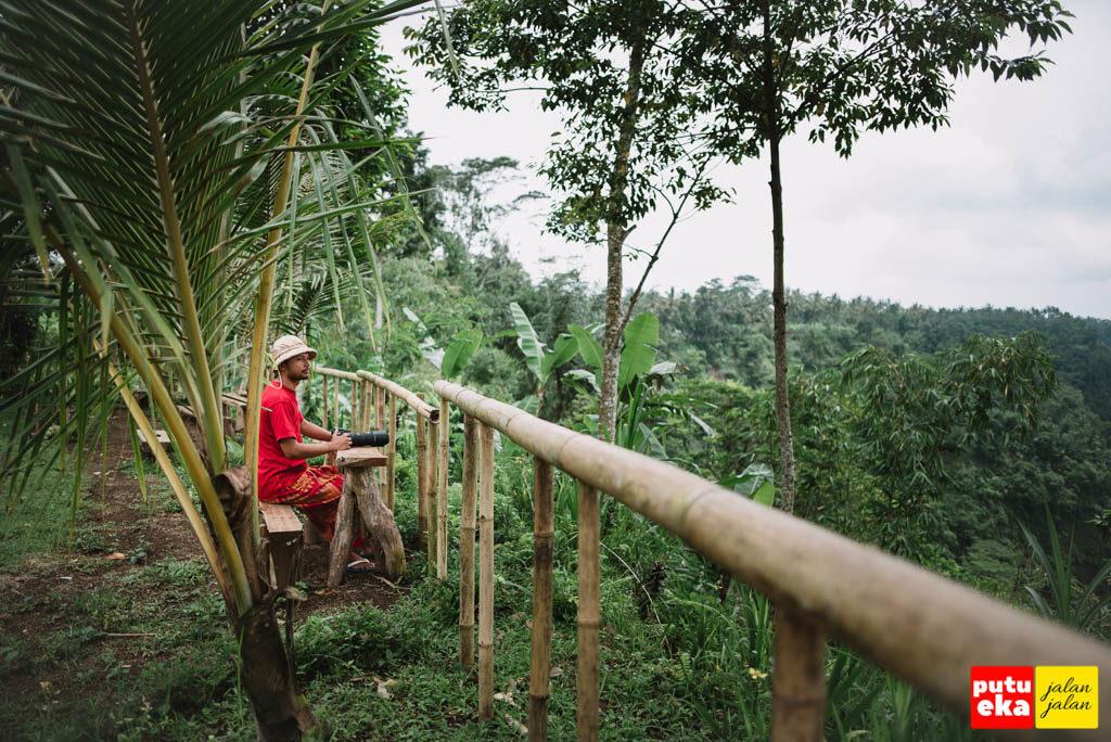 Putu Eka Jalan Jalan sedng duduk di meja kayu di tepian lembah Melangit