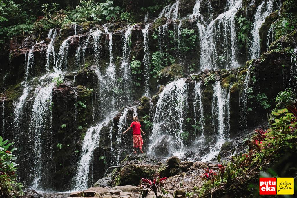 Putu Eka Jalan Jalan berada ditengah simfoni air yang jatuh dari Air Terjun Banyu Wana Amertha