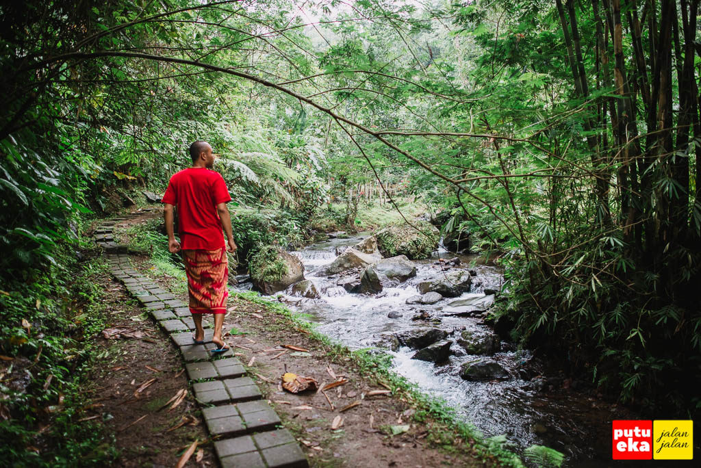 Putu Eka Jalan Jalan berjalan disepanjang aliran sungai