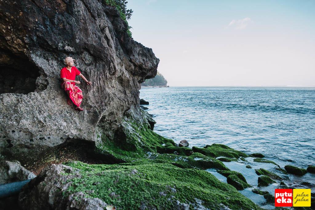Putu Eka Jalan Jalan sedang duduk di tebing karang Pantai Green Bowl