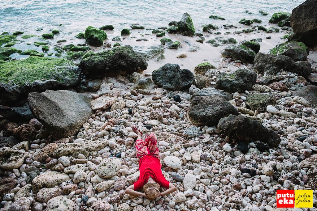 Putu Eka Jalan Jalan berbaring di atas bebatuan karang di tepi pantai