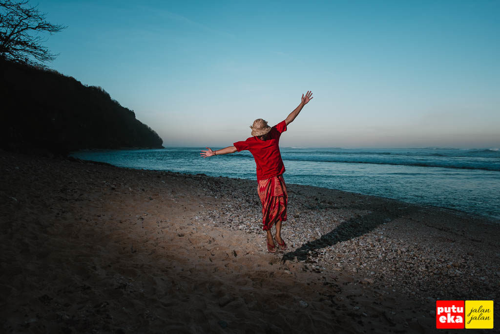 Meloncat di atas pasir pantai ketika matahari sudah terbenam
