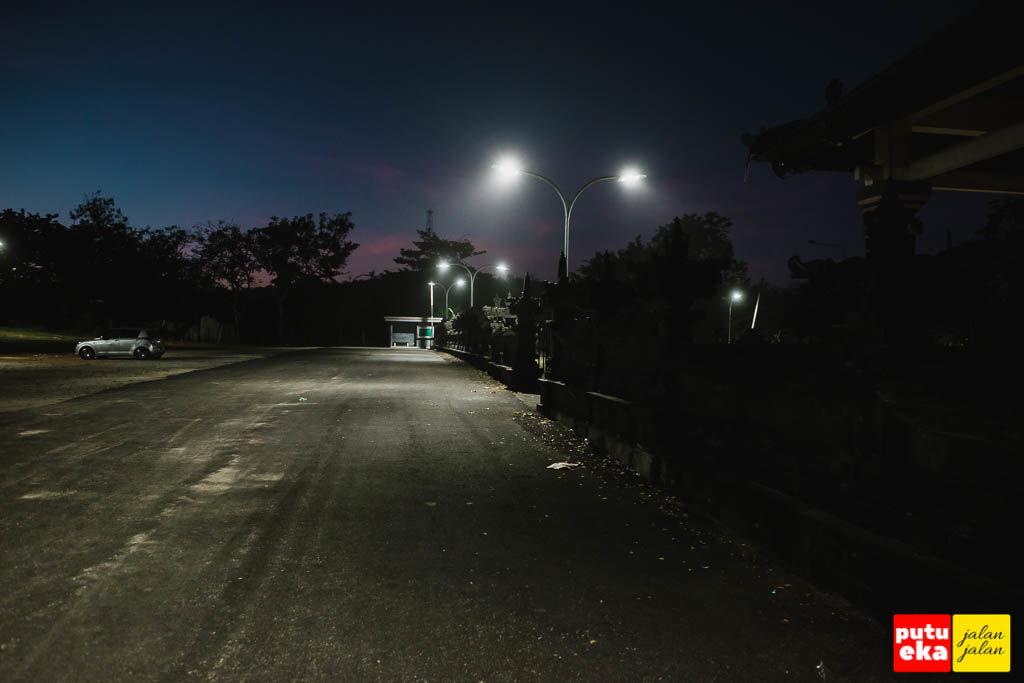 Kawasan pura dan parkiran yang diterangi lampu
