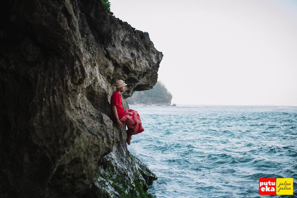 Putu Eka Jalan Jalan sedang duduk di dinding karang Pantai Green Bowl menghadap ke lautan biru