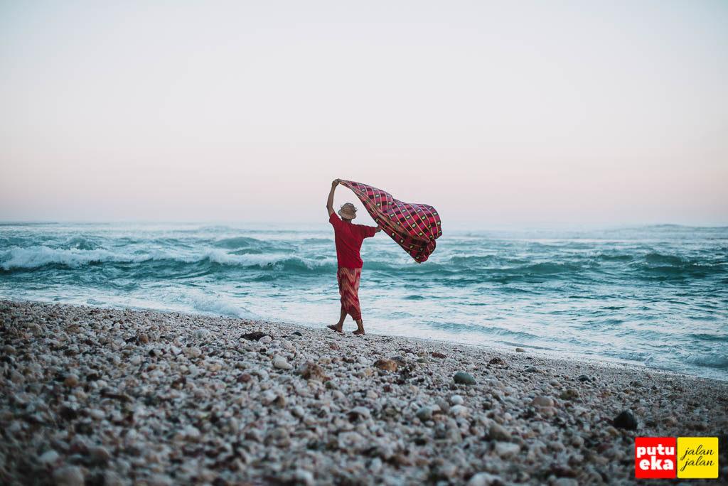 Kain Putu Eka Jalan Jalan tertiup angin ketika berjalan di bibir pantai
