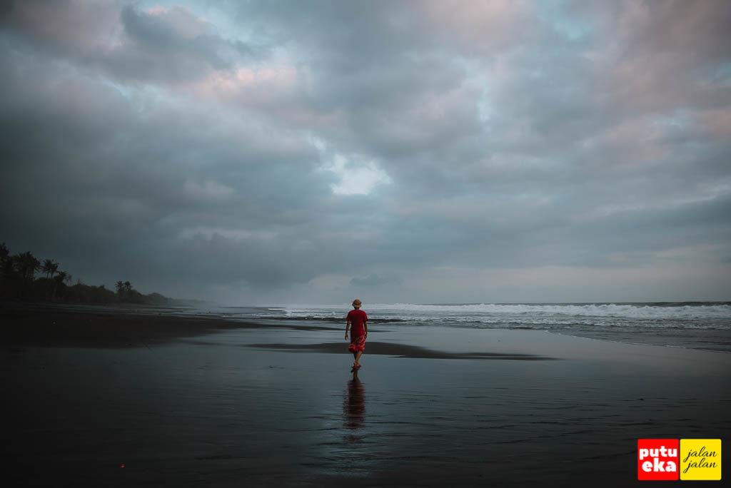 Berjalan diantara pasir hitam pantai yang basah oleh air laut