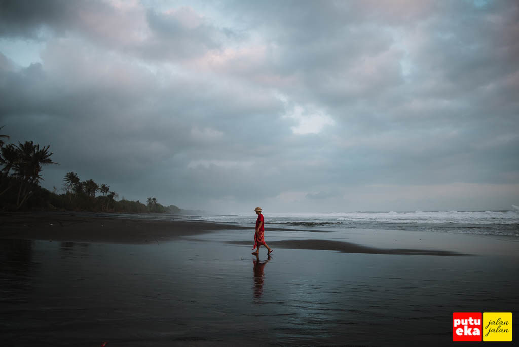 Putu Eka Jalan Jalan berjalan di hitam legamnya pasir Pantai Pasut