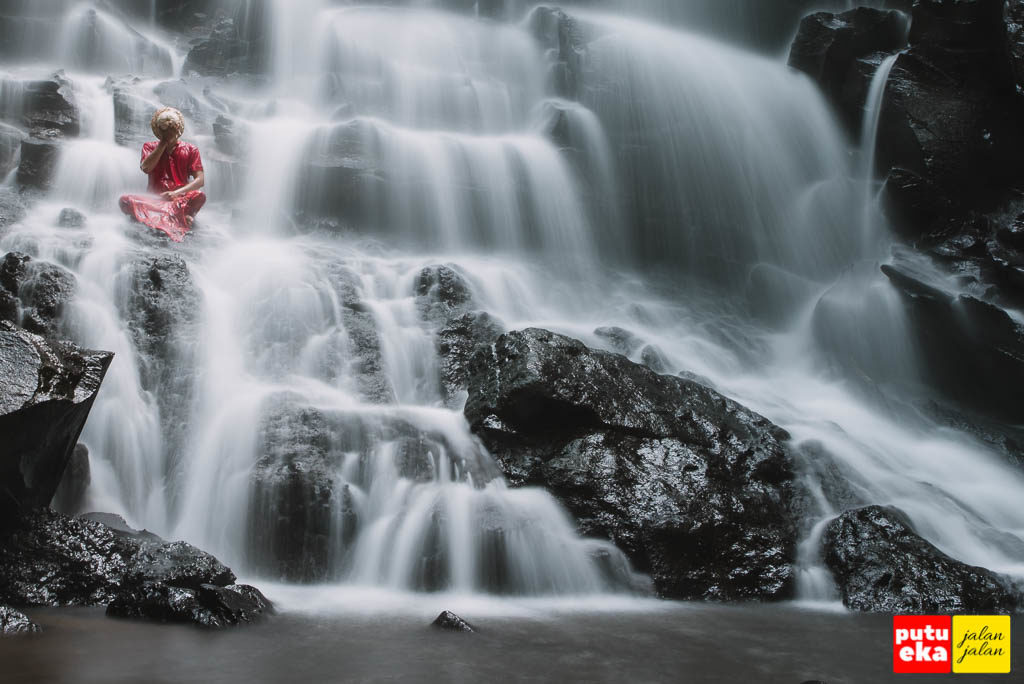 Menutupi muka agar terhindar dari cipratan air terjun