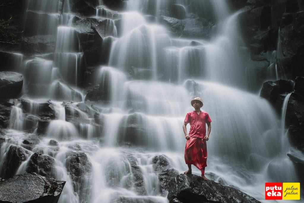 Berdiri di batu besar didepan kucuran air terjun