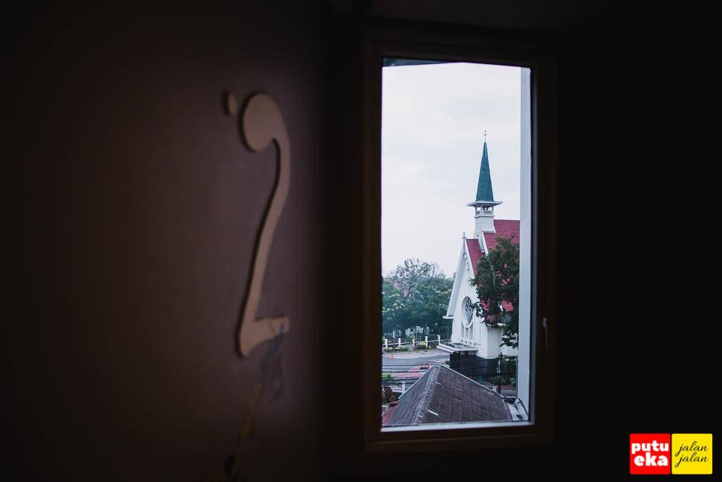 Jendela lantai dua yang mengarah ke rumah peribadatan