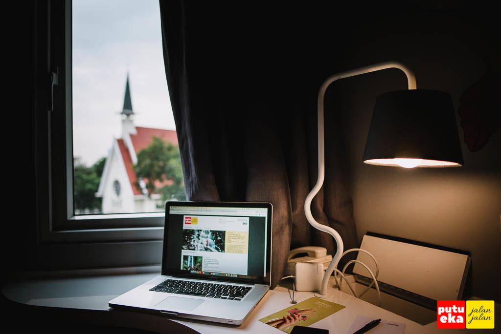 Bekerja menggunakan laptop diatas meja sambil memandang keluar jendela