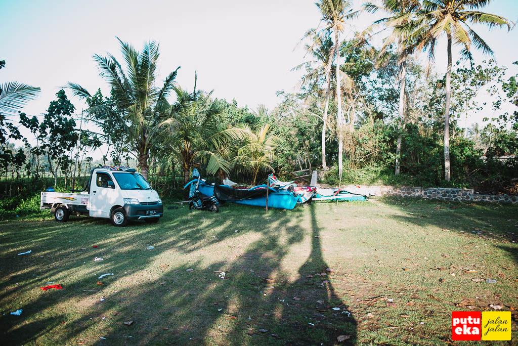 Satu mobil sedang parkir dengan perahu tradisional disampingnya