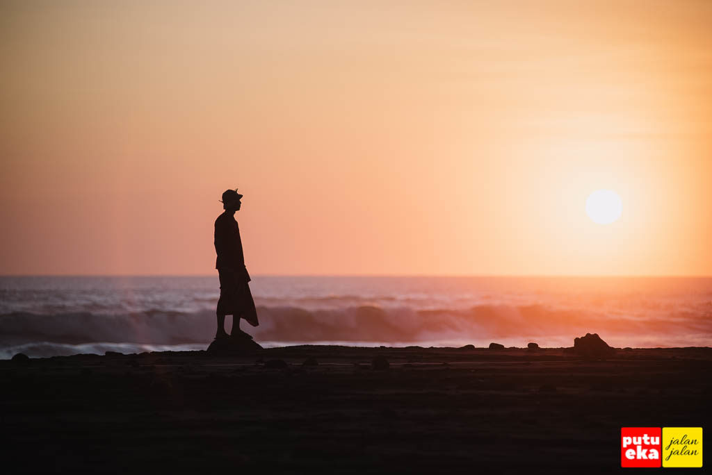 Putu Eka Jalan Jalan sedang berdiri di atas batu sambil memandang matahari terbenam
