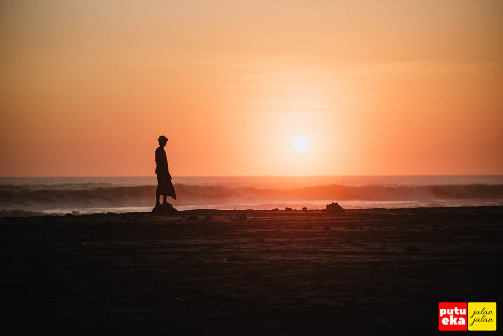 Sunset di Pantai Tampih dengan siluet Putu Eka Jalan Jalan