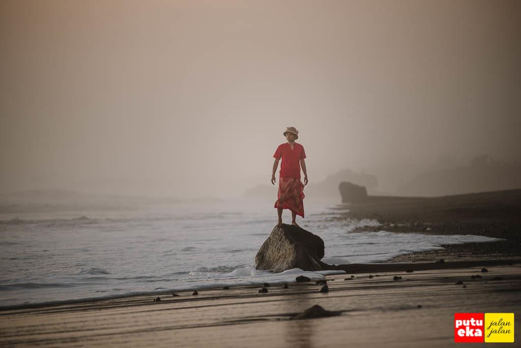 Berdiri diatas batu yang terkena sapuan ombak Pantai Tampih