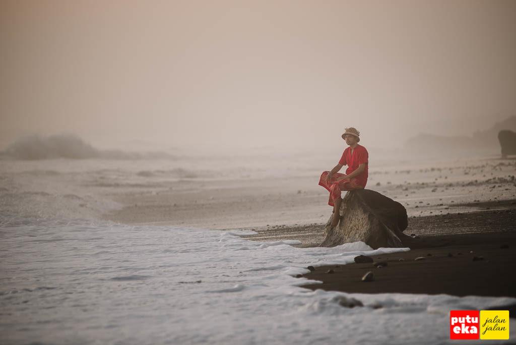 Putu Eka Jalan Jalan duduk diatas batu memandang ombak yang berkejaran diatas pasir