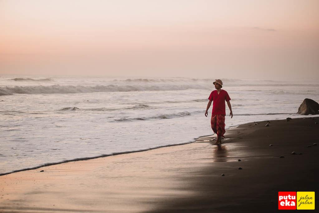 Berjalan menyusuri pantai ketika matahari terbenam tiba