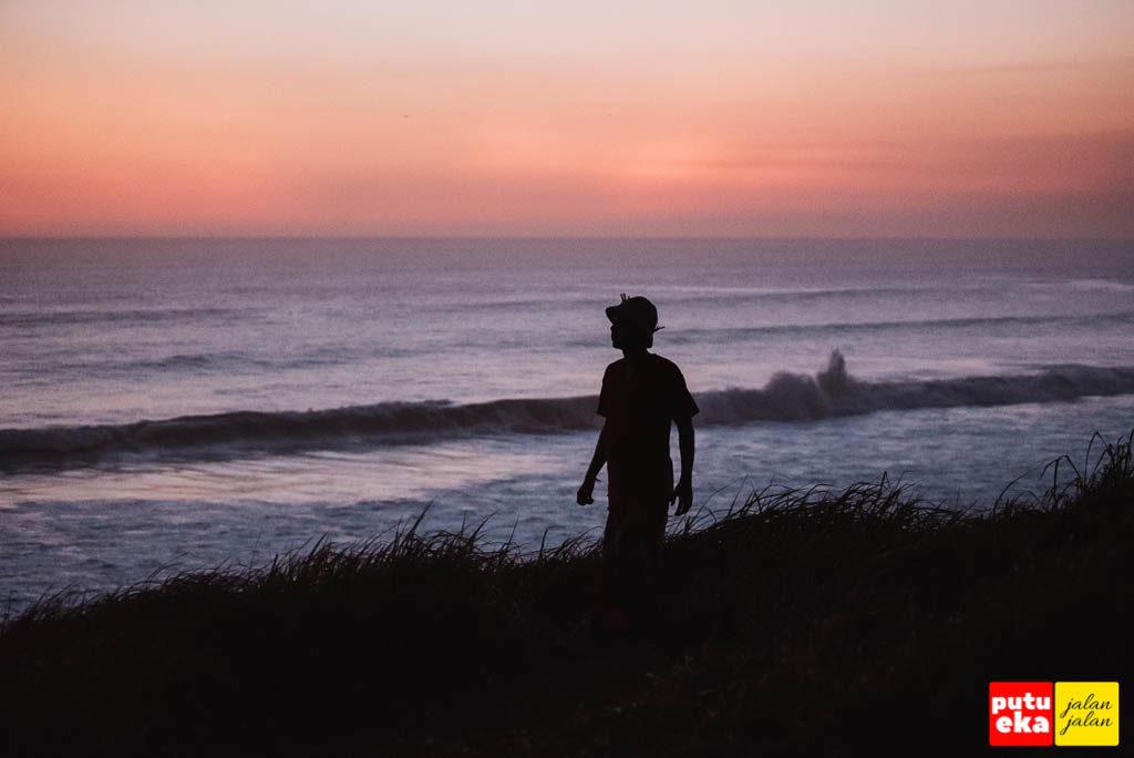 Semburat jingga serta deburan ombak pantai Tampih