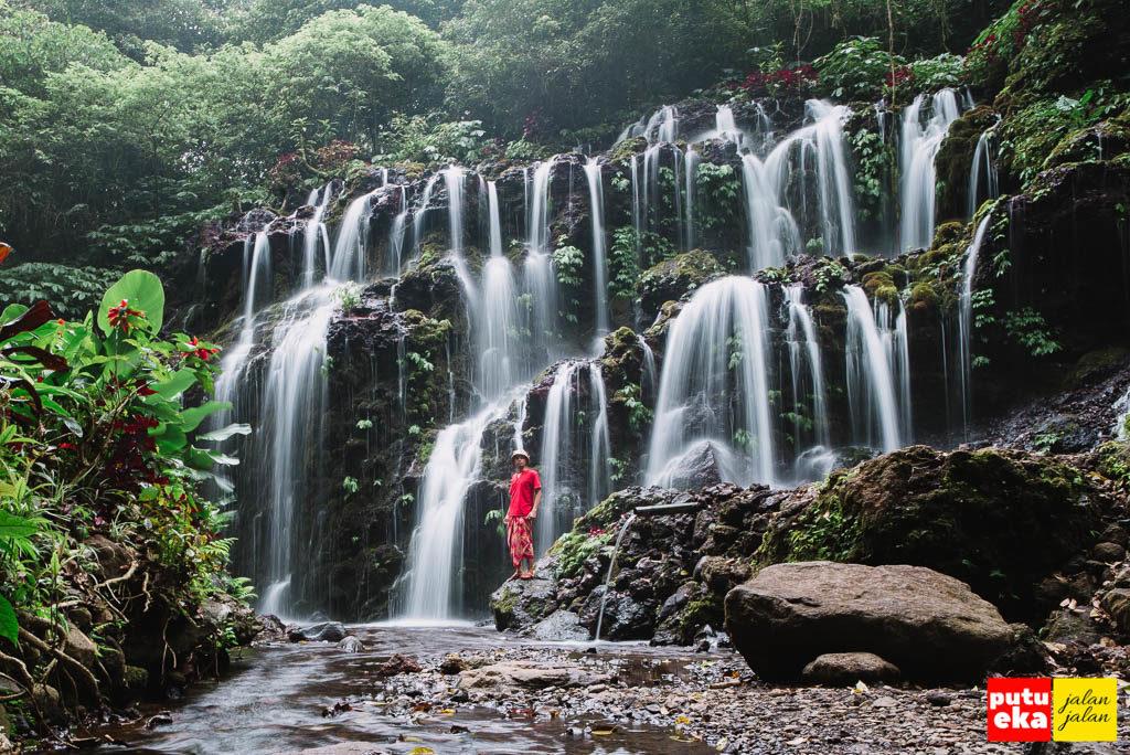 Putu Eka Jalan Jalan berada di antara aliran Air Terjun Banyu Wana Amertha