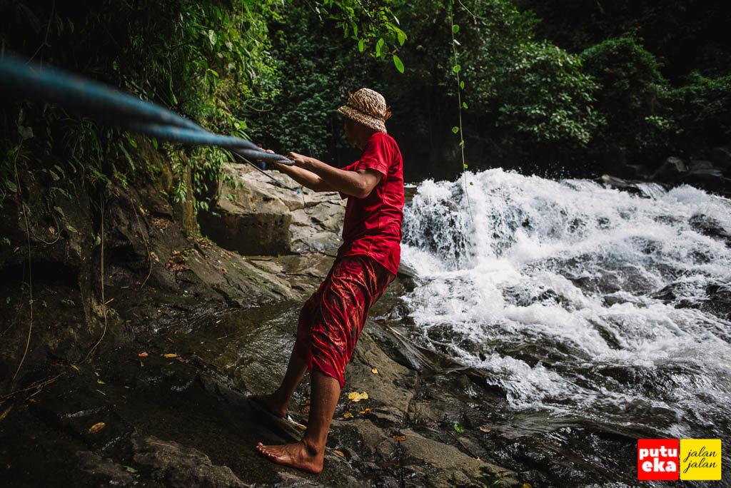 Berjalan menuju puncak air terjun dengan berpegangan pada tali