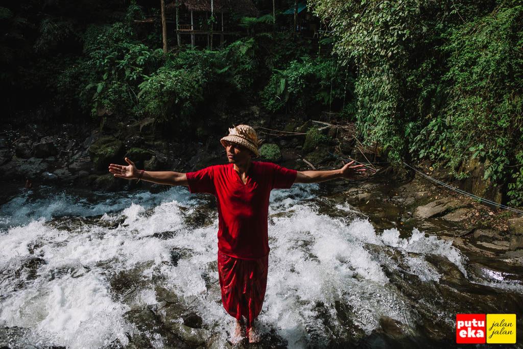 Berdiri sambil merentangkan tangan di puncak air terjun