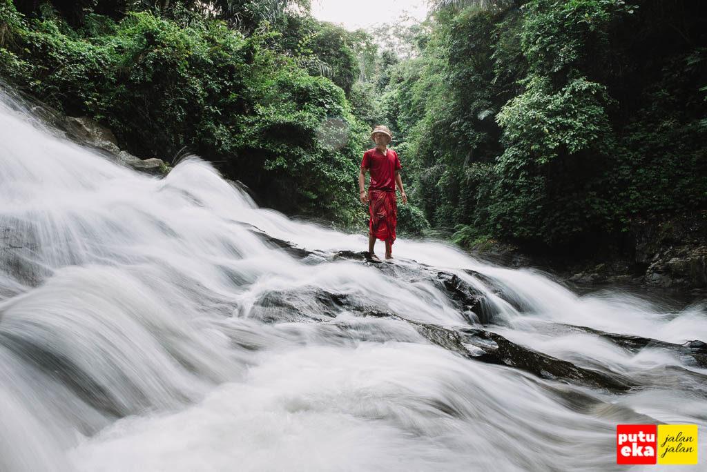 Putu Eka Jalan Jalan berdiri di tengah aliran Air Terjun Goa Rang Reng yang laksana kapas