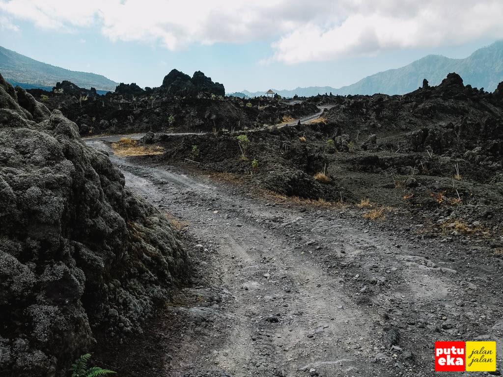 Jalan berdebu meliuk melewati batuan lava yang menghitam