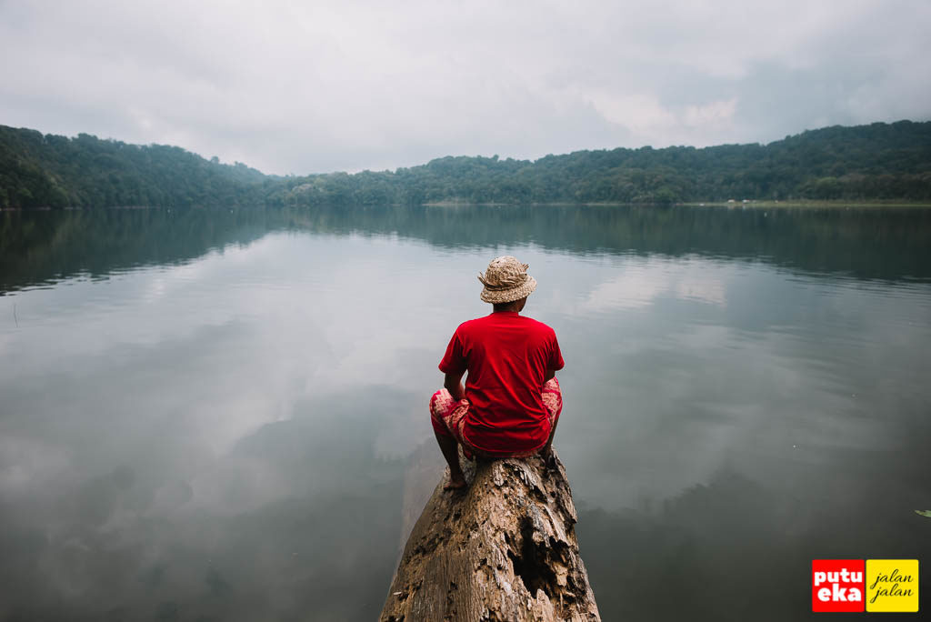 Putu Eka Jalan Jalan sedang duduk di ujung kayu memandang ke tengah Danau Tamblingan