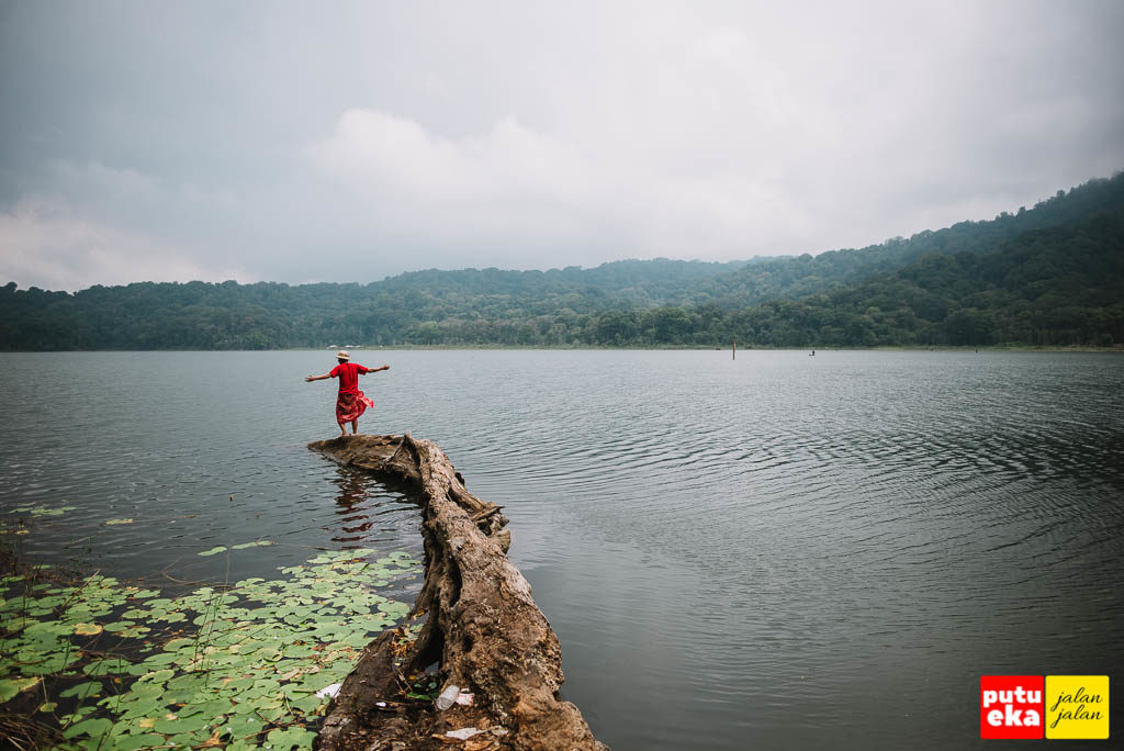 Putu Eka Jalan Jalan berada diujung pohon tumbang yang membusuk di Danau Tamblingan