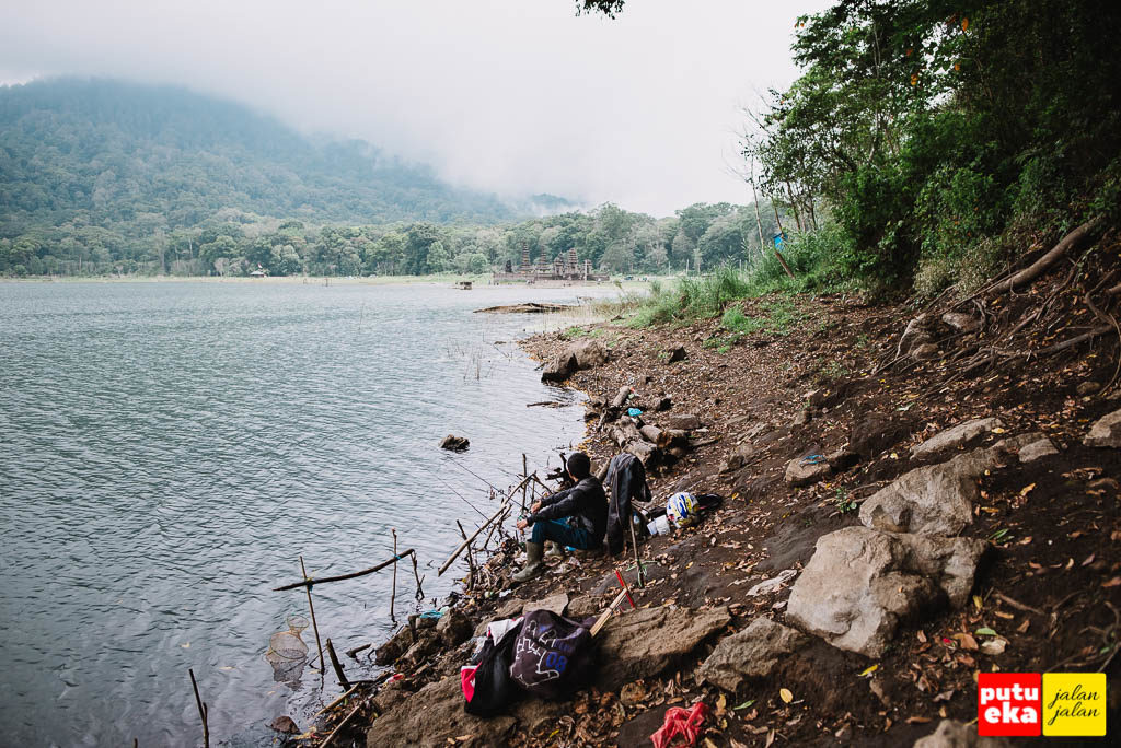 Pemancing dengan peralatan perangnya di tepi danau