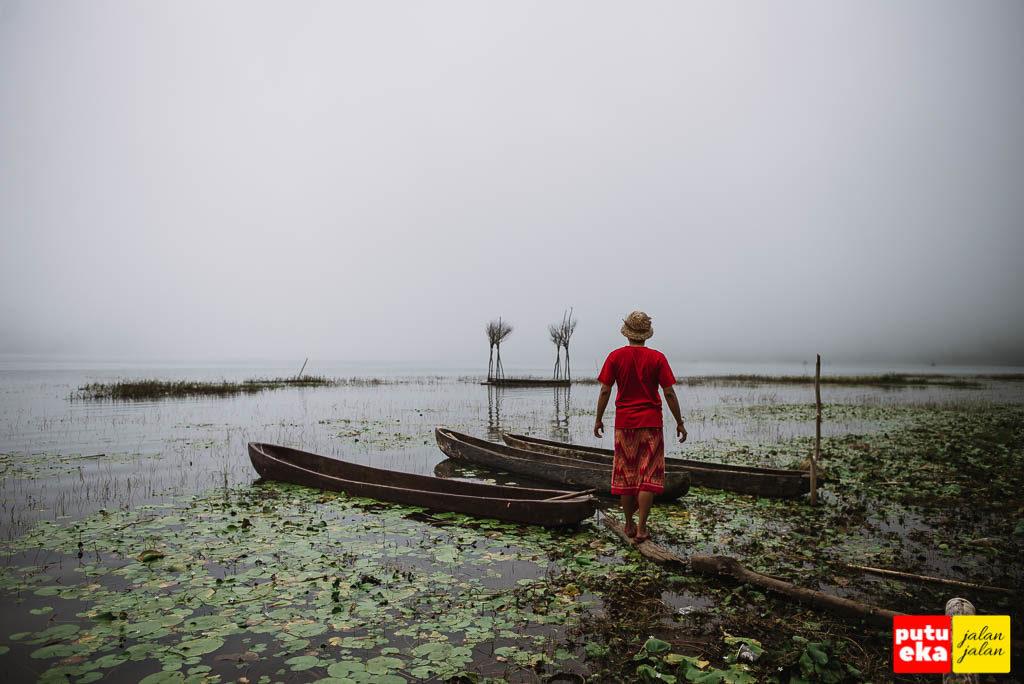 Berdiri di tepian Danau Tamblingan dengan perahu tradisional ketika kabut sedang turun menyelimuti