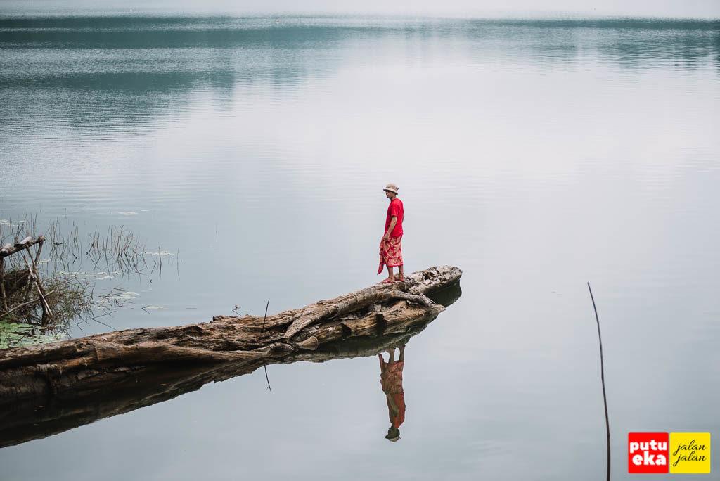 Pantulan Putu Eka Jalan Jalan di tenangnya air danau