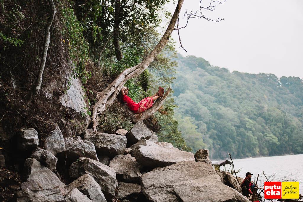 Putu Eka Jalan Jalan duduk bersantai di batang pohon sambil memandangi para pemancing