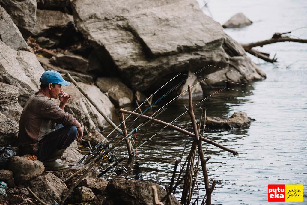 Pemancing sedang menunggu ikan menyambar umpannya