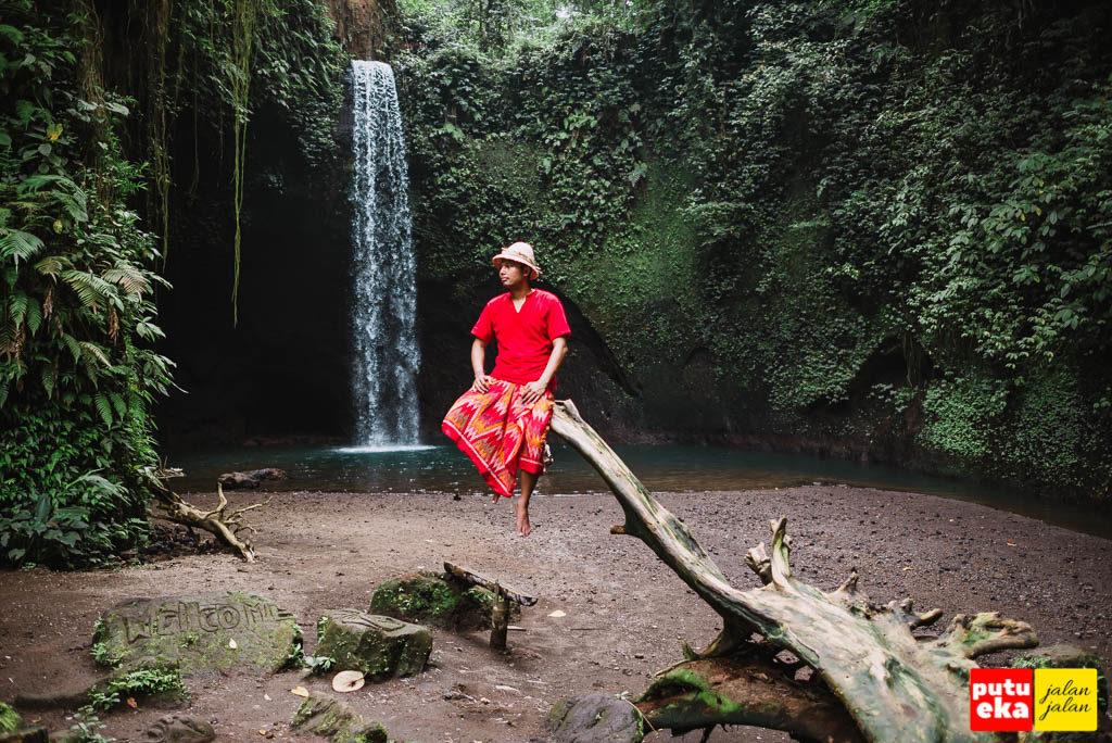 Putu Eka Jalan Jalan sedang duduk diatas pohon kering di Air Terjun Tibumana