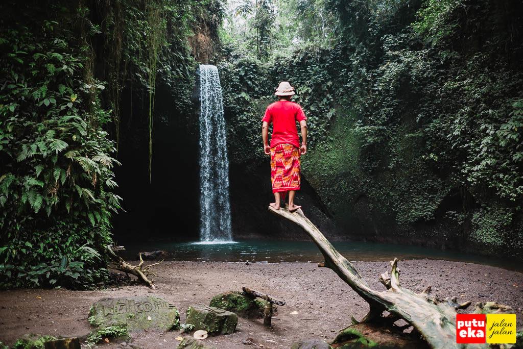 Air Terjun Tibumana dengan Putu Eka Jalan Jalan sedang berdiri diatas pohon kering
