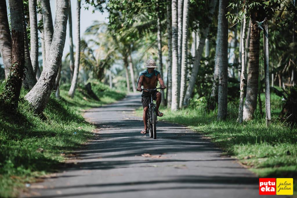 Bapak petani sedang lewat dengan mengayuh sepedanya