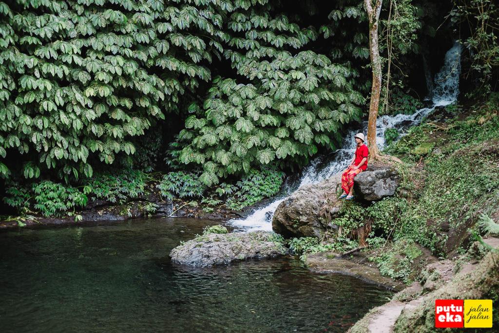 Duduk sambil menikmati ketenangan air terjun Banyumala