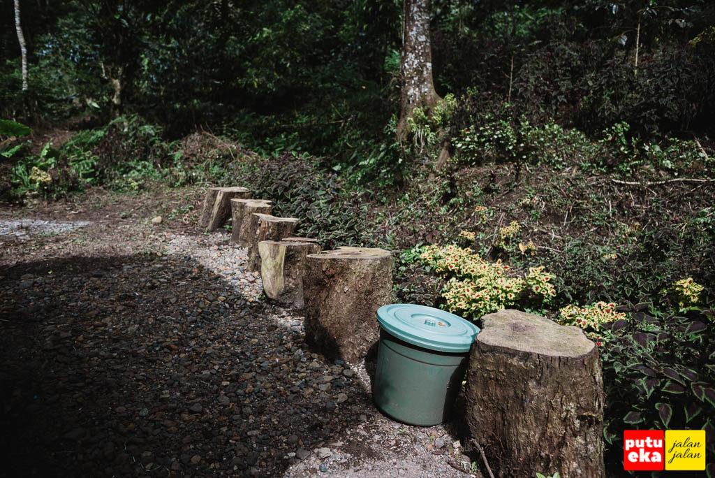 Tempat sampah diantara gelondong kayu