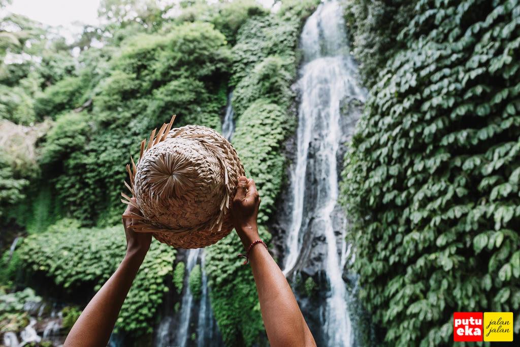 Air terjun Banyumala dengan topi dari anyaman