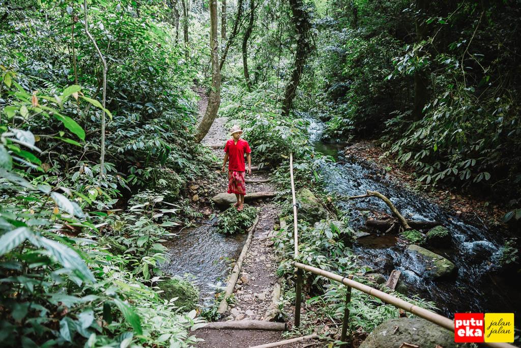 Putu Eka Jalan Jalan menyusuri aliran air dari air terjun