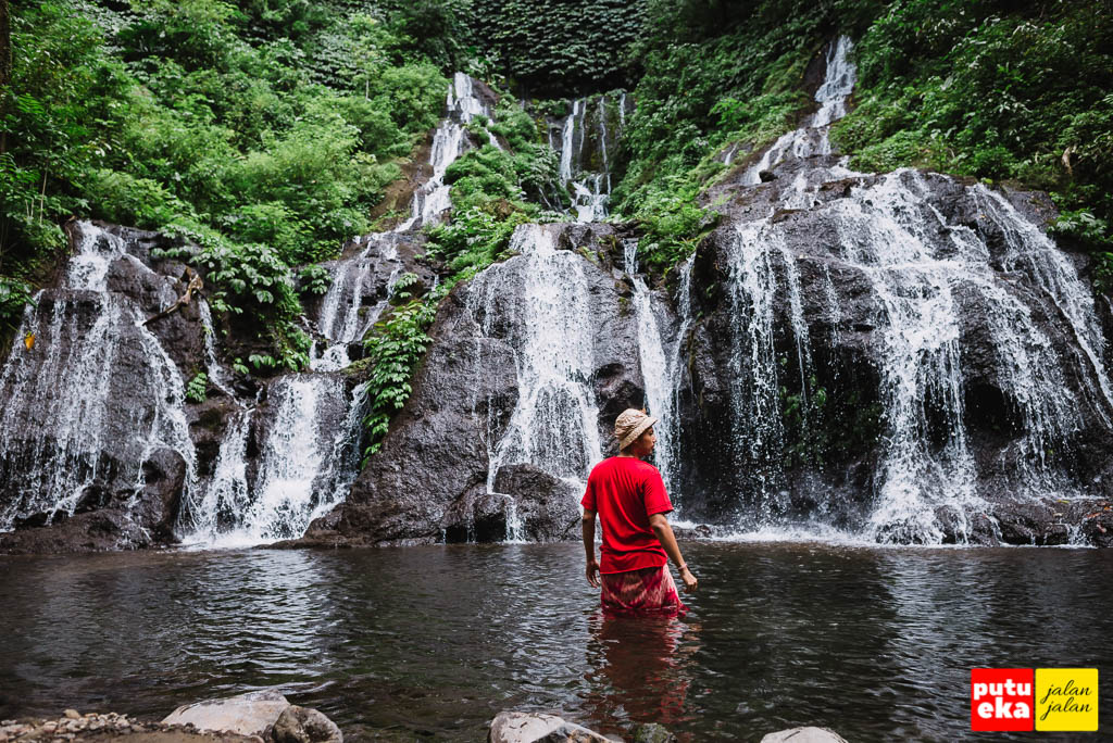 Berdiri ditengah kolam air dari air terjun Pucak Manik yang segar